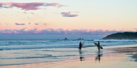 Two surfers at Suffolk Park Beach, Byron Bay.